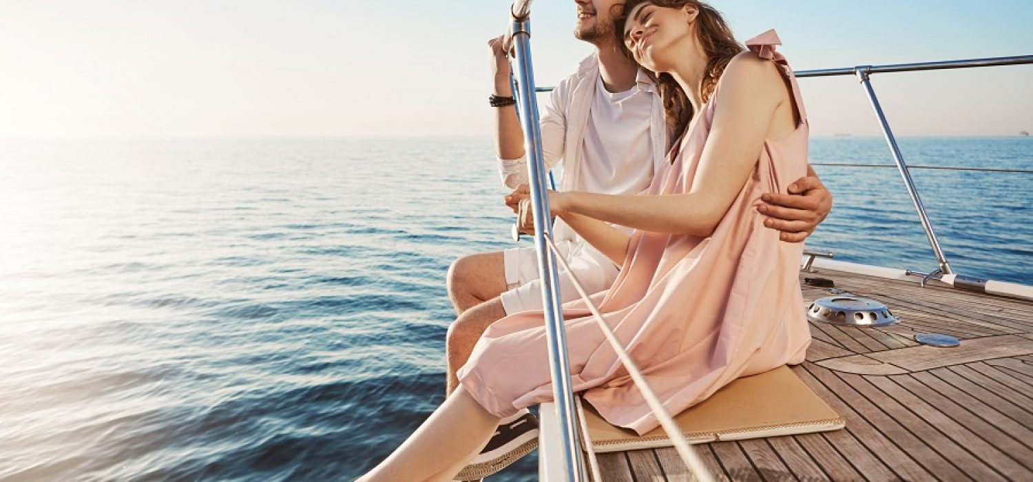 Happy beautiful adult couple sitting on side of yacht, watching at seaside and hugging while on vacation. Tan might fade but such memories you share with one you love, last forever. Love and vacation concept.